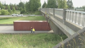 Container truck meets overpass in Langley