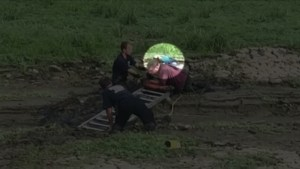 Police rescue man with parrot on his shoulder after he gets stuck in mud pit
