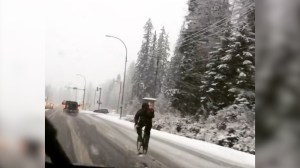 Cyclist rides through snowy Whistler weather