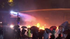 Hong Kong police fire water cannons at protesters as fires set off, petrol bombs used