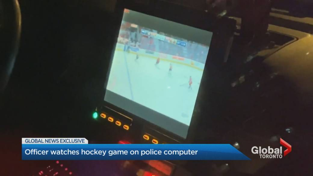 Toronto police officer watches NHL hockey game on cruiser computer at double shooting scene