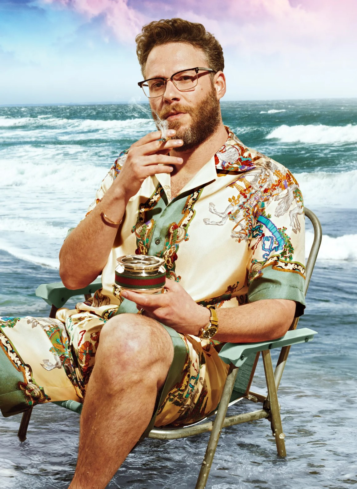 seth rogen sitting in a beach chair at the edge of the ocean smoking