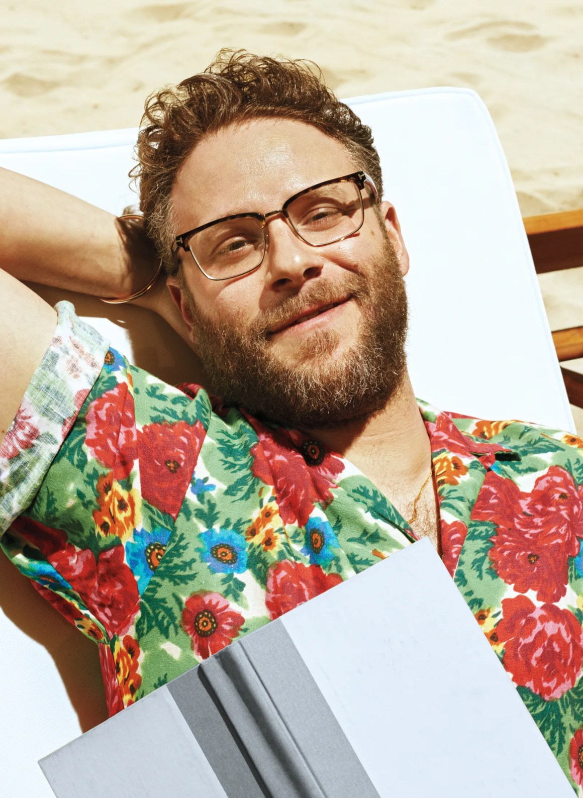 seth rogen lounging on a beach chair with an open book resting on his chest