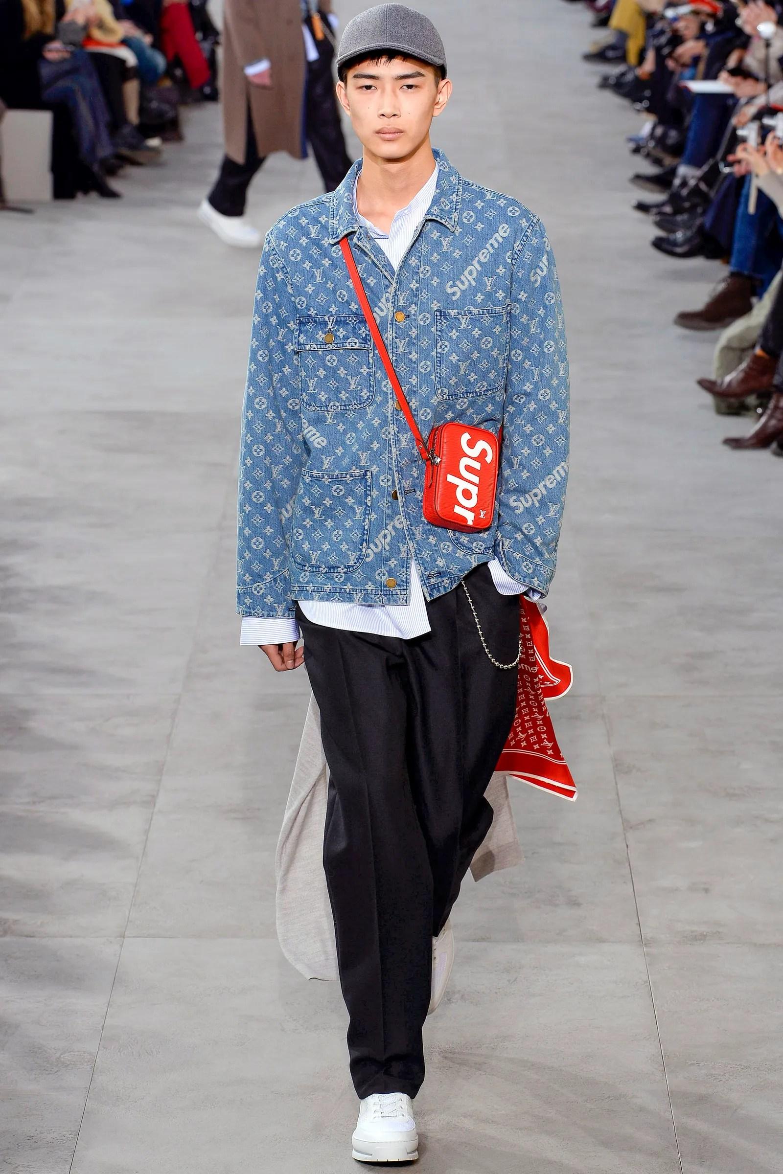 A model walking down a runway dressed in a denim coat and black pants