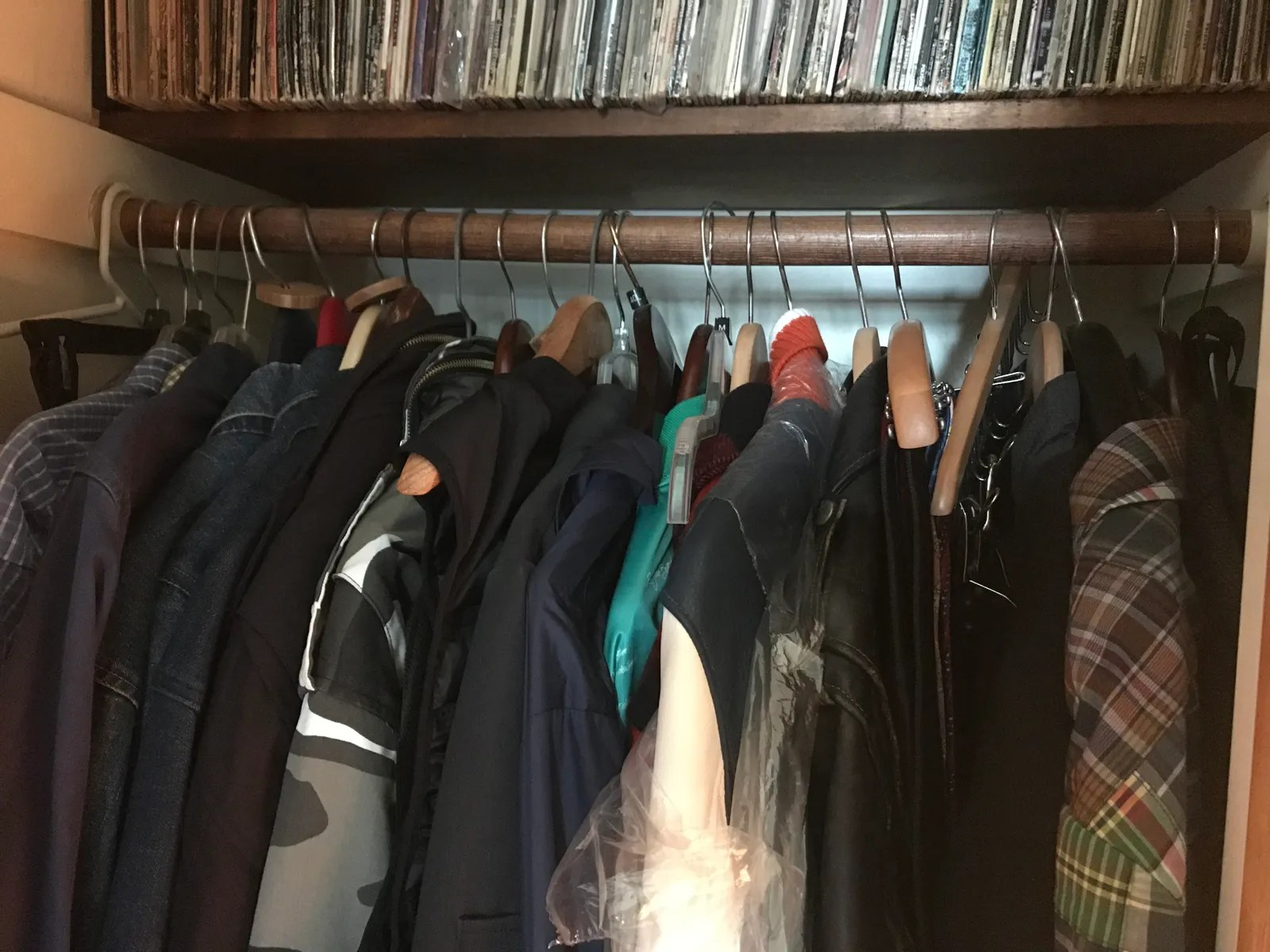 a rack in a storage unit with many jackets on hangers and a shelf of records above