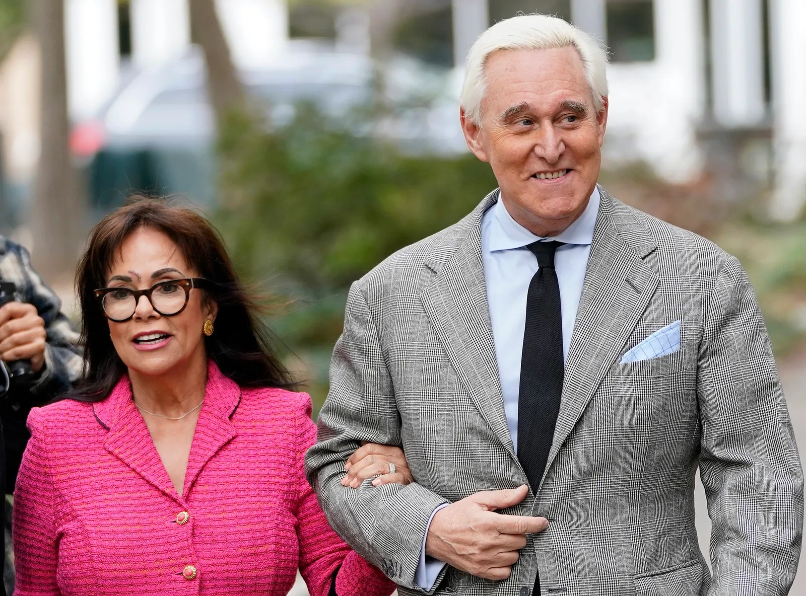 Roger Stone from the waist up walking outside wearing a grey suit and black tie next to a woman wearing a bright pink...