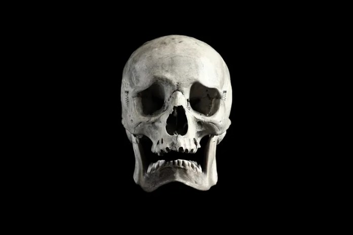 A frowning human skull on a black background