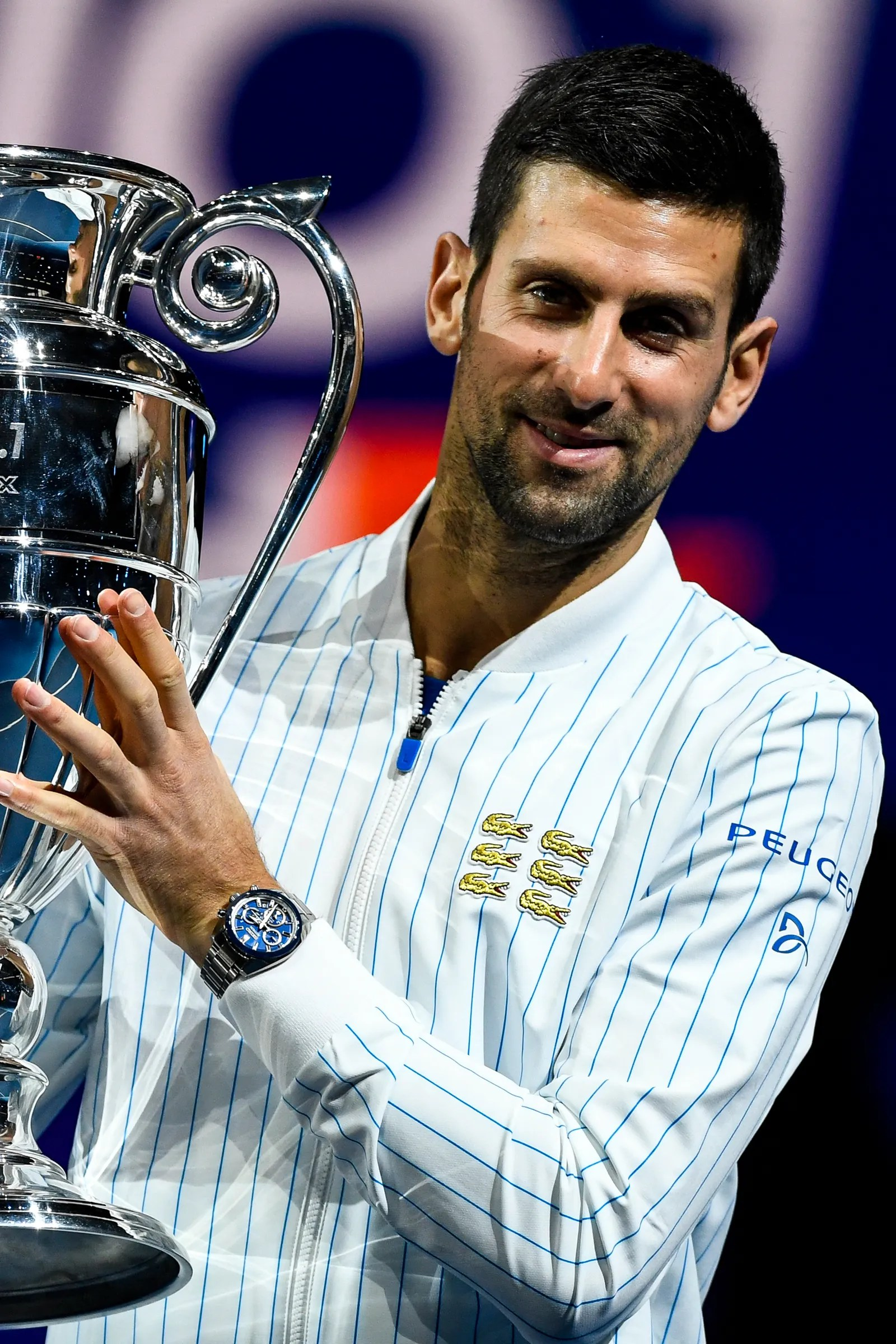 Novak Djokivic smiling and holding a big trophy