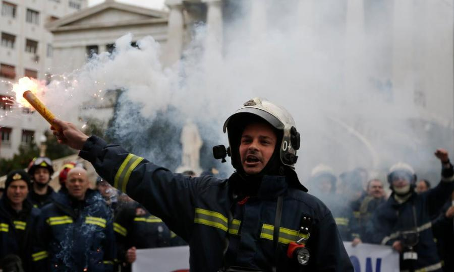 Greek firefighters holding flares take part in a protest in central Athens, Greece, on 8 February 2017
