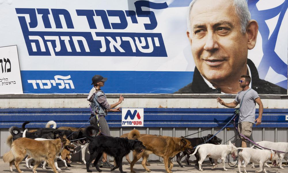 Dog walkers argue beneath a Netanyahu campaign billboard in Tel Aviv.