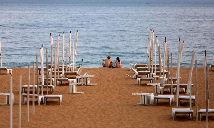 A couple is seen next to empty hammocks during the coronavirus  pandemic in downtown Albufeira, Portugal July 20, 2020.
