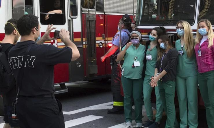 Medical staffers ask a New York City firefighter to photograph them in front of the firetrucks gathering for the 7pm appreciation clap for health care workers amid the coronavirus pandemic, Saturday, 2 May 2020, in New York.