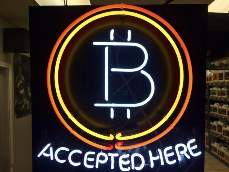 A neon sign hanging in the window of Healthy Harvest Indoor Gardening in Hillsboro, Ore., shows that the business accepts bitcoin as payment.