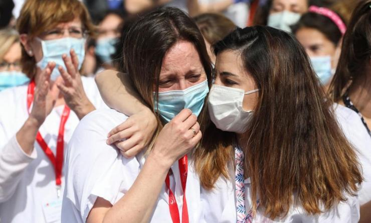 Health workers react after the last patients were discharged from a temporary hospital in Madrid before its closure.