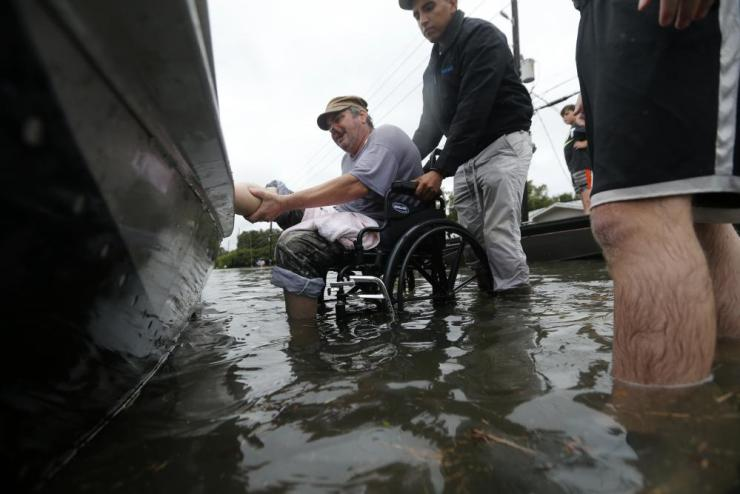 Mike Henry, center, lifts his leg onto a boat as members of the Louisiana Department of Wildlife and Fisheries helps rescue him during flooding from Tropical Storm Harvey in Orange, Texas.