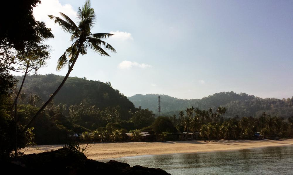 Sandy beach and mountain backdrop at Tioman Island, Malaysia.