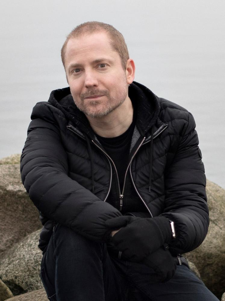aral balkan sitting on rocks on a shoreline in close up