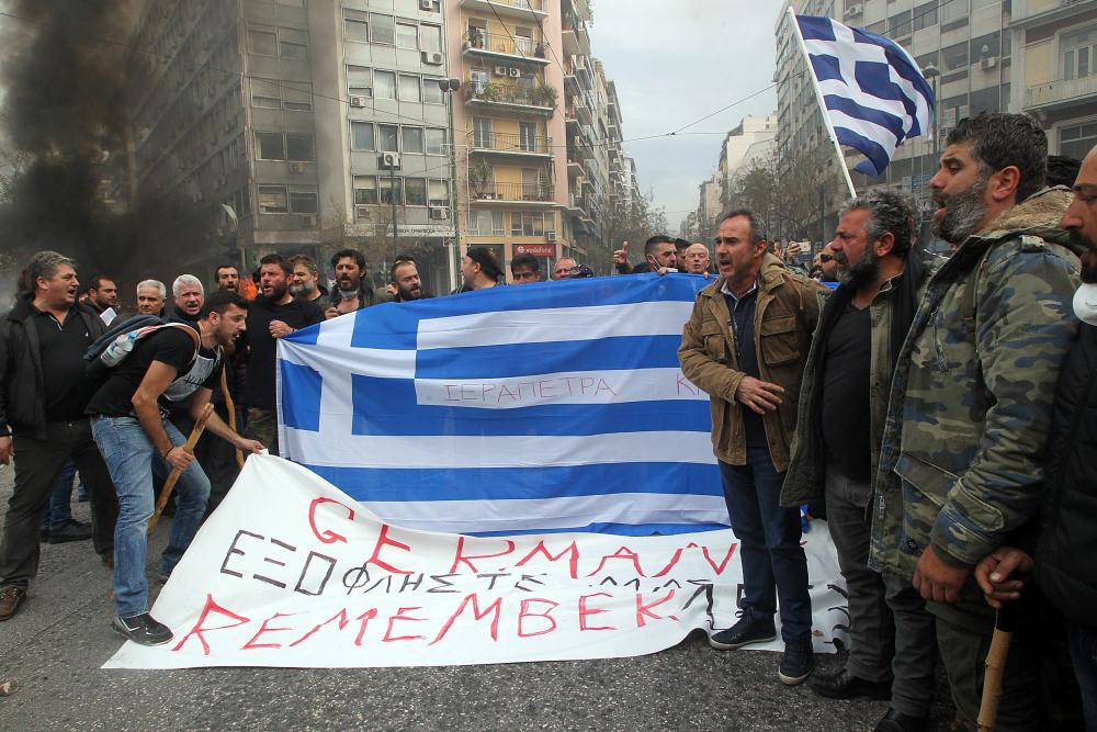 Farmers hold a banner reading 'Germany - Redeem us now - Remember 1953' during a protest outside the Agriculture Ministry in Athens, Greece, 12 February 2016. Farmers from all over Greece organise a massive protest in central Athens requesting that the government withdraws its proposed social security and pension reform plan. Protesters are expected to meet in Athens and walk towards the Parliament on Syntagma square, where they will set up tents to house farmers who will remain there for the entire weekend. EPA/PANTELIS SAITAS