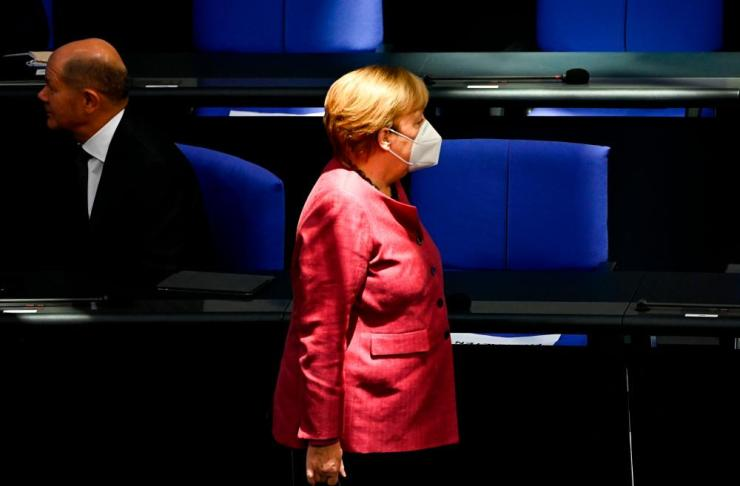 Angela Merkel wears a face mask as she walks past finance minister and vice-chancellor Olaf Scholz to take her seat at the Bundestag.
