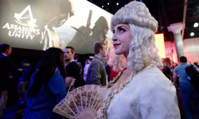 "Although ""booth babes"" are now widely discouraged, publishers now use both professional and amateur cosplayers to attend stands dressed as game characters. Here's Marie Antoinette from Assassin's Creed Unity"