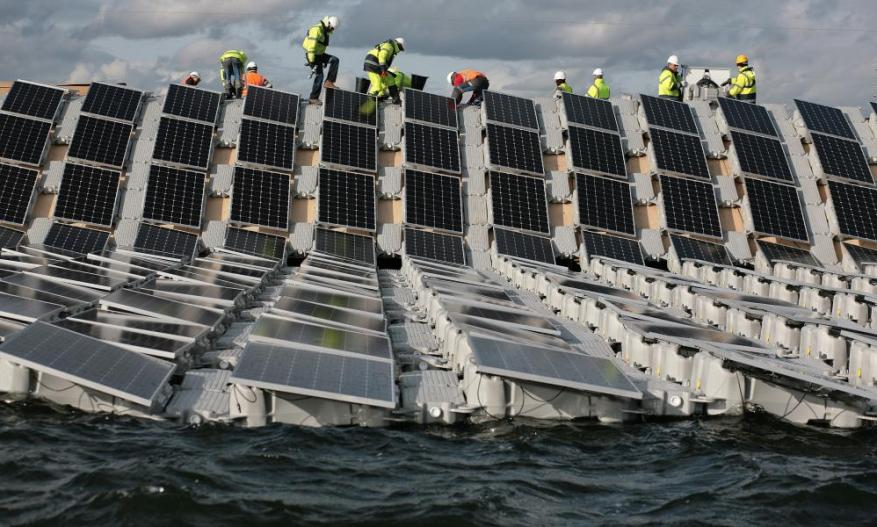 Crews install panels that form the world's largest floating solar power array in the Queen Elizabeth II reservoir near Heathrow.