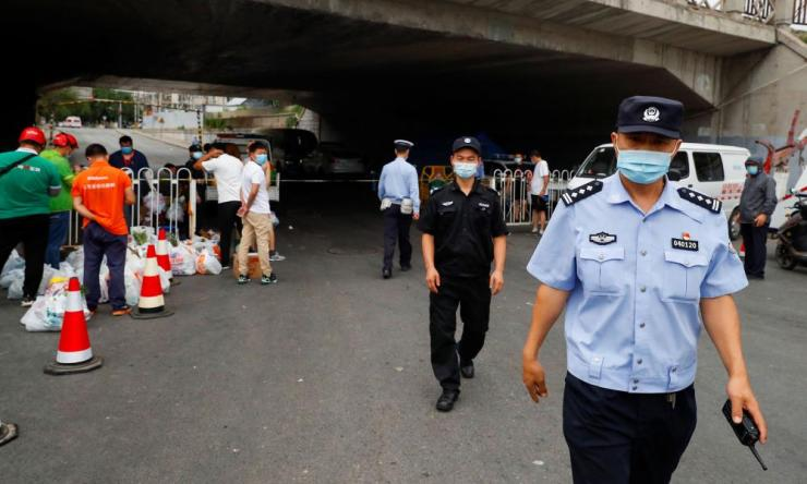 People deliver food near a residential compound that is under lockdown in the Fengtai district, Beijing, on 17 June 2020.