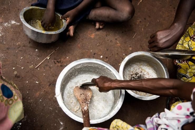 People eat at the Katanika displacement settlement