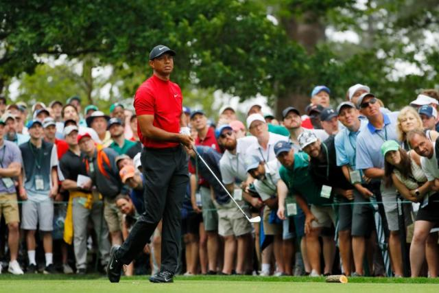 Woods watches his shot on the 4th tee.