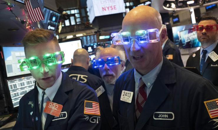 Stock traders wear New Year's 2020 party glasses at New York Stock Exchange, Tuesday, Dec. 31, 2019