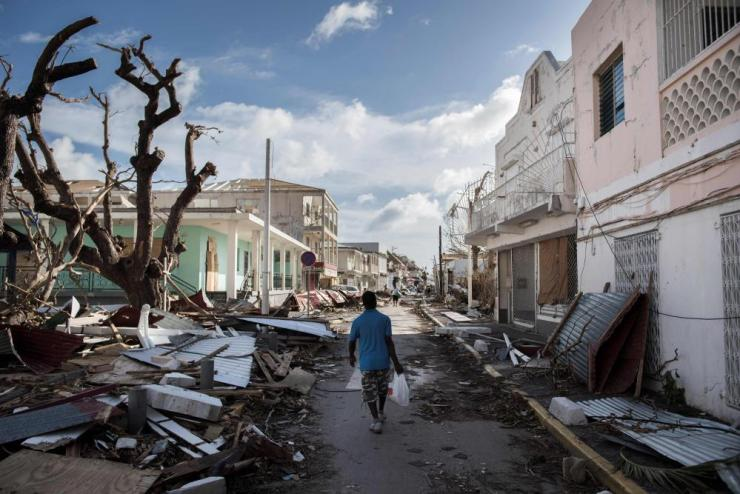 TOPSHOT - A man walks on a street covered in debris after hurricane Irma hurricane passed on the French island of Saint-Martin, near Marigot on September 8, 2017. Officials on the island of Guadeloupe, where French aid efforts are being coordinated, suspended boat crossings to the hardest-hit territories of St Martin and St Barts where 11 people have died. Two days after Hurricane Irma swept over the eastern Caribbean, killing at least 17 people and devastating thousands of homes, some islands braced for a second battering from Hurricane Jose this weekend. / AFP PHOTO / Martin BUREAUMARTIN BUREAU/AFP/Getty Images
