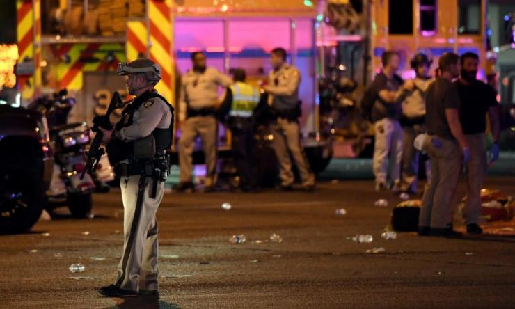 Las Vegas Metropolitan Police Department officer stands in the intersection of Las Vegas Boulevard and Tropicana Avenue after a mass shooting at a country music festival