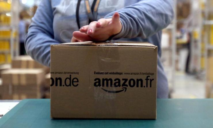 AnAmazon worker taping a parcel.