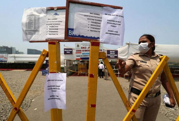A policewoman gestures past notices about the shortage of Covid-19 vaccine at a vaccination centre in Mumbai, India, on 28 April, 2021.