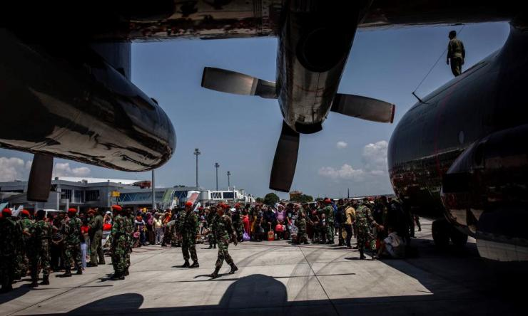 A crowd of people gather at the airport in Palu in the hope of fleeing