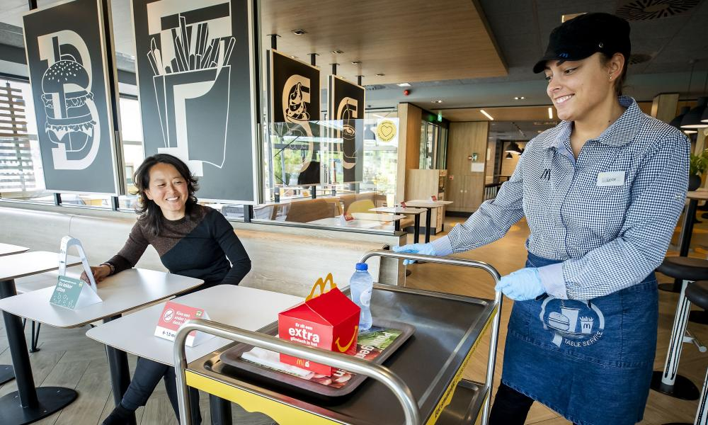 A McDonalds' employee uses a trolley to deliver food to a 'customer' at a test location in a restaurant at in Arnhem, The Netherlands.