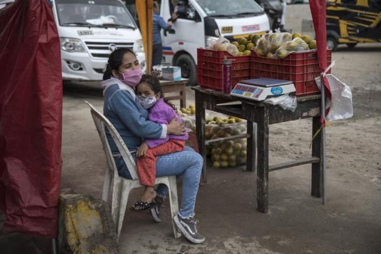 Maria Garcia embraces her daughter Sofia, while selling oranges on a street in Lima.