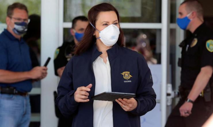 Gretchen Whitmer wears a face mask as she arrives to address the media about flooding along the Tittabawassee River in May.