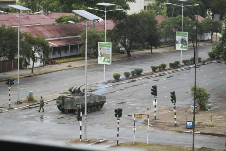 """A military tank is seen with armed soldiers on the road leading to President Robert Mugabe's office in Harare, Wednesday, Nov. 15, 2017. Overnight, at least three explosions were heard in the capital, Harare, and military vehicles were seen in the streets. On Monday, the army commander had threatened to """"step in"""" to calm political tensions over the 93-year-old Mugabe's possible successor. (AP Photo/Tsvangirayi Mukwazhi)"""