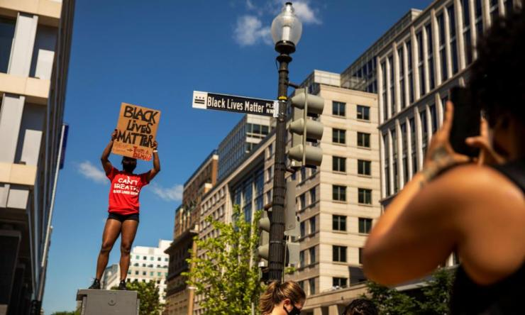 A woman holds a Black Lives Matter aloft near the White House on Sunday