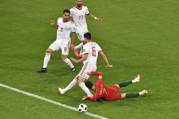 Cristiano Ronaldo falls after a challenge by Saeid Ezatolahi.