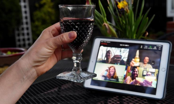 A woman lifts her glass and cheers with friends during a virtual happy hour amid the coronavirus  crisis on April 8 in Virginia, in the US.