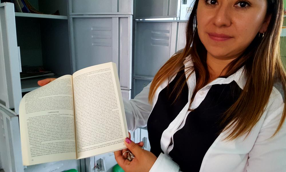 Teacher Angelica Rivera with a fine-print copy of Gulliver's Travels.