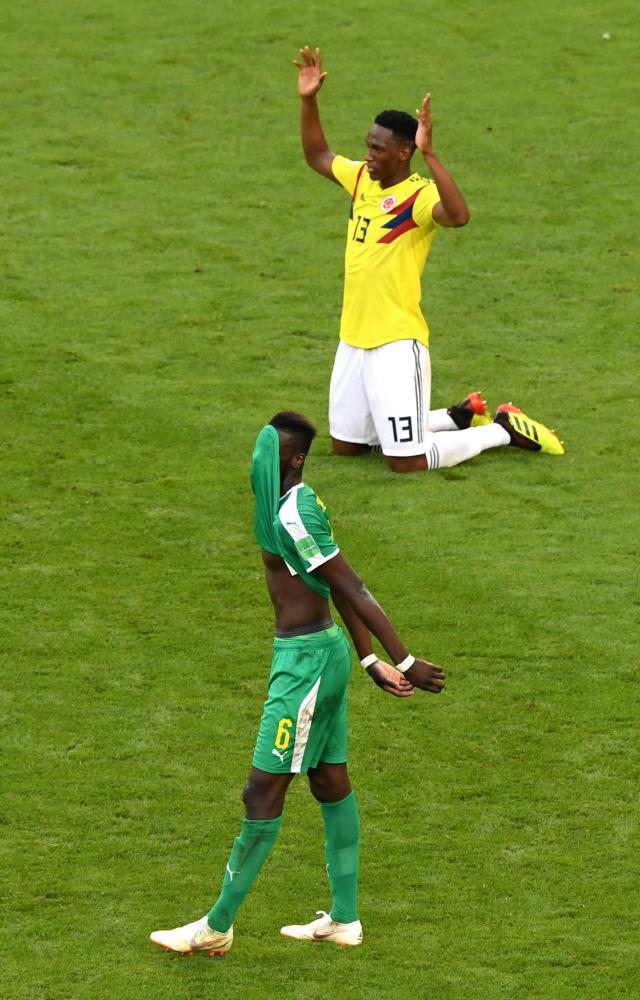 Salif Sane of Senegal looks dejected as Yerry Mina of Colombia celebrates.