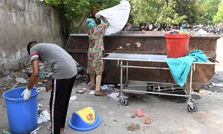 Cleaning staff throw medical waste into a bin at Guru Nanak Dev hospital, Amritsar.