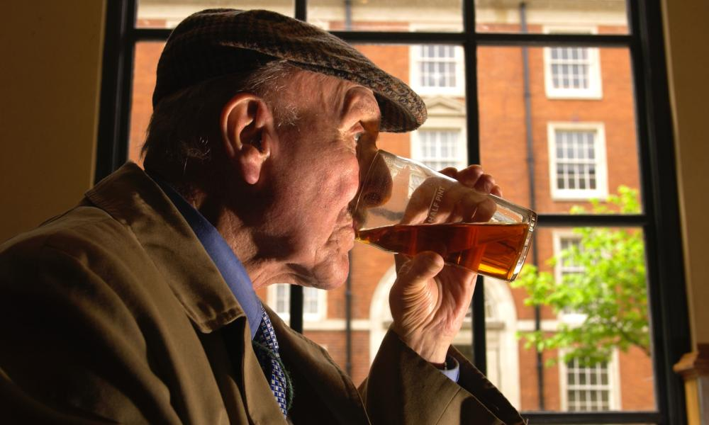 Old man drinks in a pub.