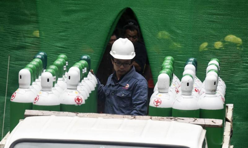 Rescue workers move air tanks at the Tham Luang cave area as operations continue.