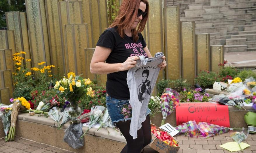 Paroo Streich holds a shirt of boxing legend Muhammad Ali as she pays her respects at the Muhammad Ali Center in Louisville, Kentucky.