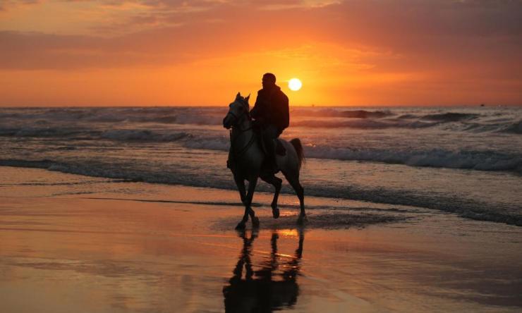 A Palestinian horseman enjoys the last sunset of 2019 on a beach in Gaza City.
