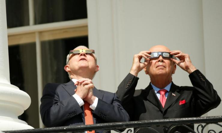 Sessions and Ross watch the solar eclipse from the Truman Balcony at the White House in Washington.