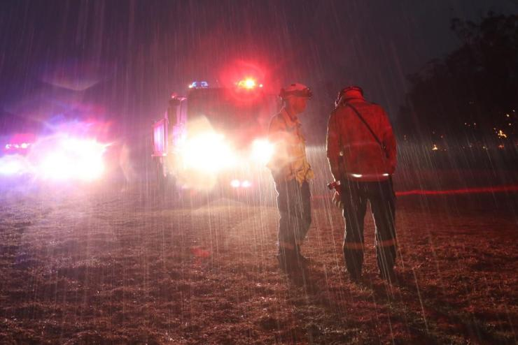 RFS crews fight a fire at the Green Wattle Creek fire near Bargo NSW tonight as it starts to rain.